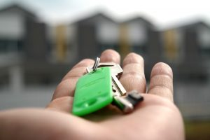 Outstretched hand holding keys. Home buyer beginners guide.